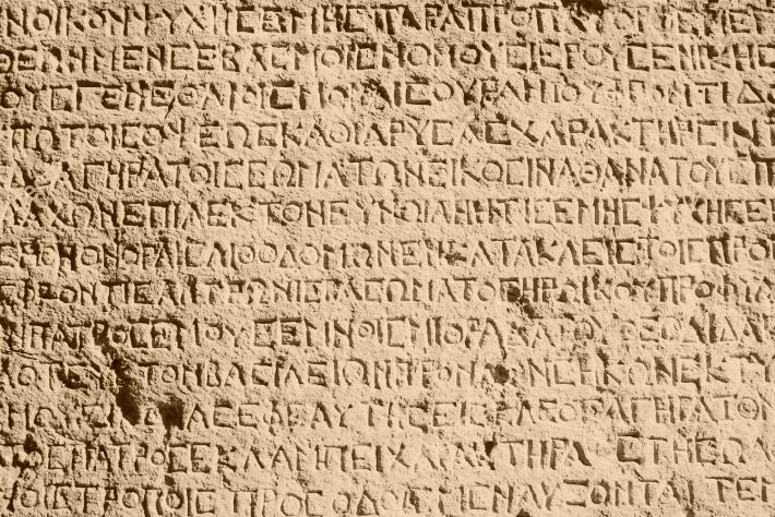 stock-photo-ancient-greek-writing-chiseled-on-stone-92164756